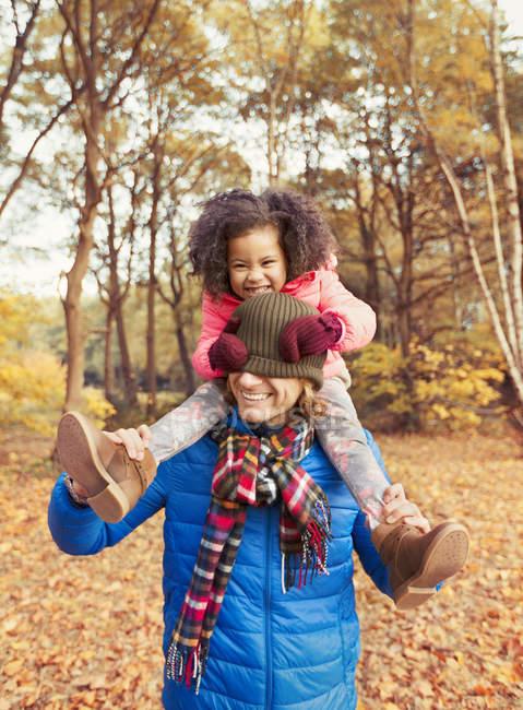Retrato juguetona hija tirando de media gorra sobre los ojos de los padres en el parque de otoño - foto de stock