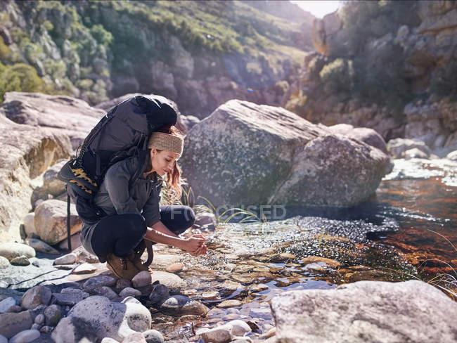 Mujer joven con mochila senderismo, lavándose las manos en el arroyo soleado - foto de stock