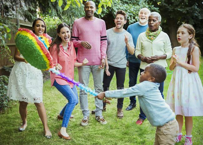 Мультинациональная многонациональная семья аплодирует мальчику, который бьет пиньяту на дне рождения — стоковое фото