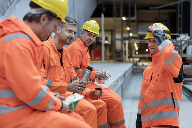 Construction workers eating lunch at construction site — Stock Photo