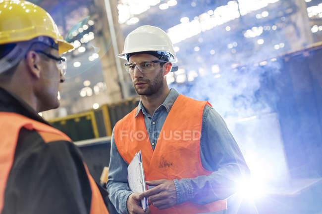 Сталеві працівників говоримо один одному заводі — стокове фото