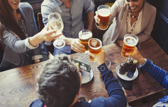 Vista aérea amigos comemorando, brindando cerveja e copos de vinho à mesa no bar — Fotografia de Stock