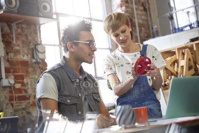Designers discussing prototype cog in workshop — Stock Photo