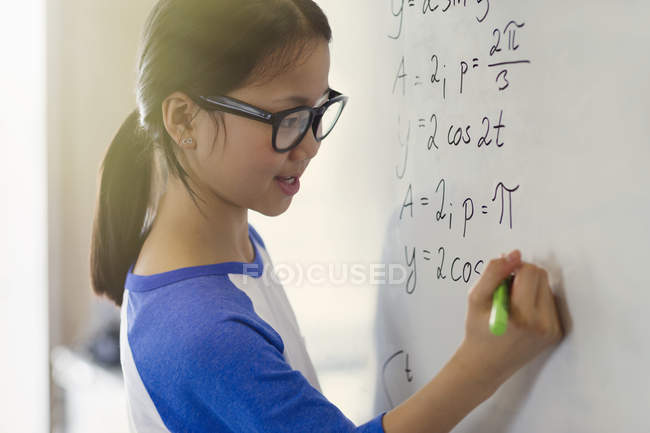 Portrait smiling, confident girl student solving physics equations at whiteboard in classroom — Stock Photo