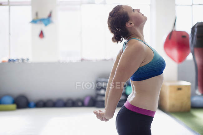 Side view of woman stretching chest in gym — Stock Photo