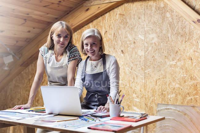 Портрет посміхаючись художників з ноутбук та малюнки в студії — стокове фото
