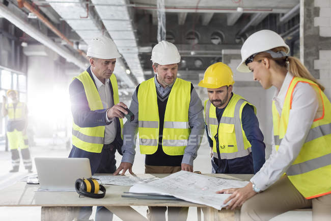 Инженеры просматривают чертежи на строительной площадке — стоковое фото