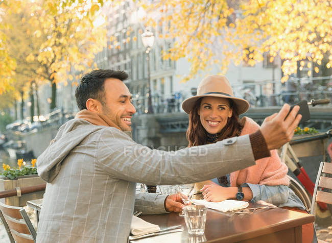 Молодая пара делает селфи с камерой телефона в осеннем кафе на тротуаре — стоковое фото