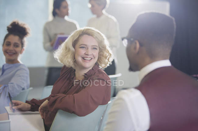 Smiling businesswoman turning and listening to businessman in conference audience — Stock Photo
