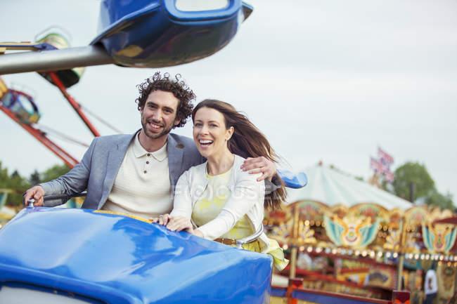 Couple profitant de rouler sur le carrousel en parc d'attractions — Photo de stock