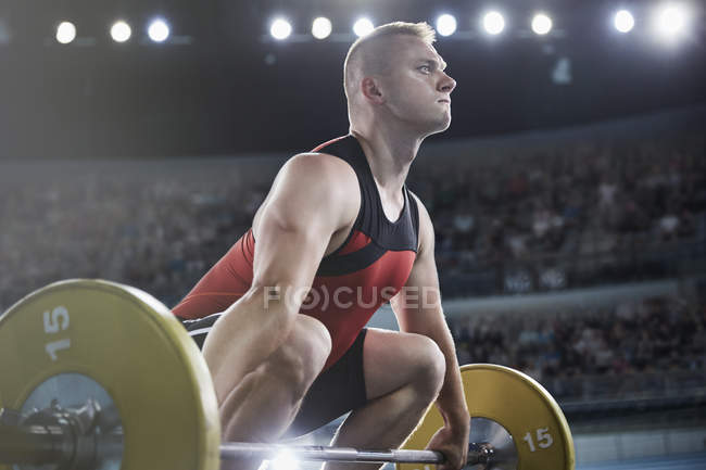 Focused male weightlifter lifting barbell — Stock Photo