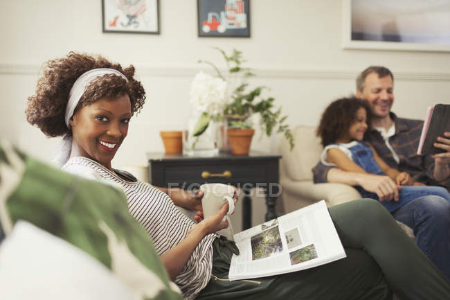 Portrait smiling woman relaxing with tea and magazine on sofa — Stock Photo