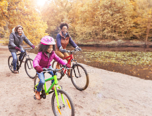 Young family bike riding along pond in woods — Stock Photo
