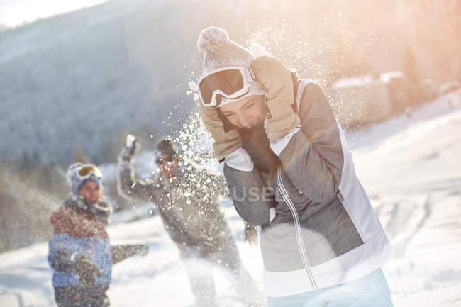 Играющие друзья-лыжники наслаждаются снежным поединком на снежном поле — стоковое фото