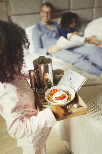 Girl serving breakfast in bed and card to father on Fathers Day — Stock Photo