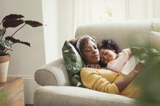 Serene mother and daughter napping and cuddling on sofa — Stock Photo