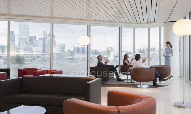 Business people clapping for businesswoman leading meeting in highrise urban lounge — Stock Photo