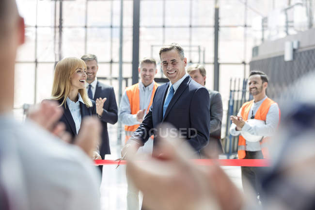 Smiling businessman and businesswoman cutting ribbon at new construction site ceremony — Stock Photo
