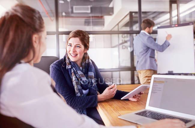 Улыбаясь предпринимателей с цифрового планшета и ноутбука, говорить в обслуживание совещания Конференции — стоковое фото
