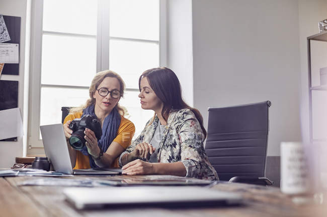 Female photographers with digital camera working at laptop in office — Stock Photo