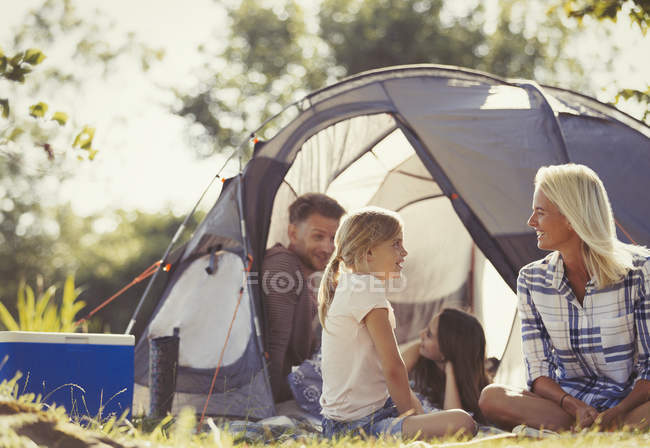 Family talking and relaxing outside tent at sunny campsite — Stock Photo