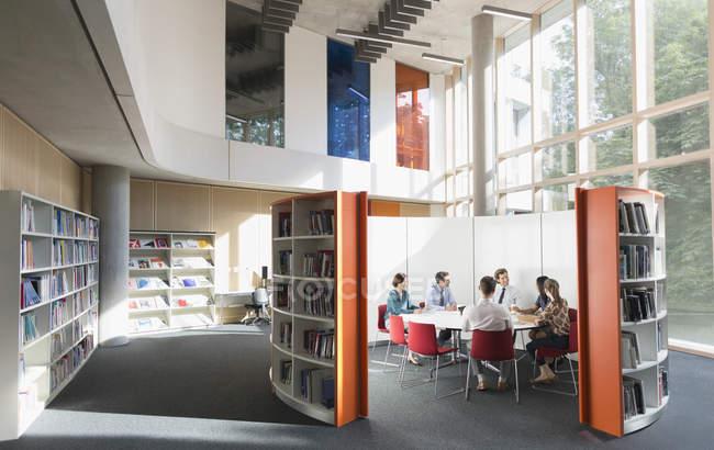 Hommes d'affaires réunis à la table ronde à la bibliothèque ouverte — Photo de stock