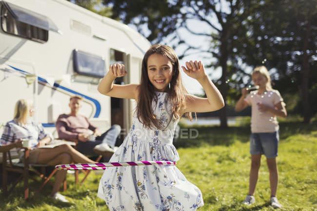 Портрет посміхається дівчина спінінг в пластикових Хооп за межами сонячний будинок — стокове фото