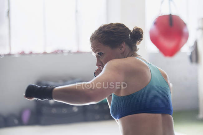Determined female boxer shadowboxing in gym — Stock Photo