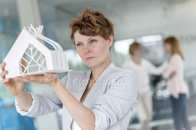 Focused female architect examining model in office — Stock Photo