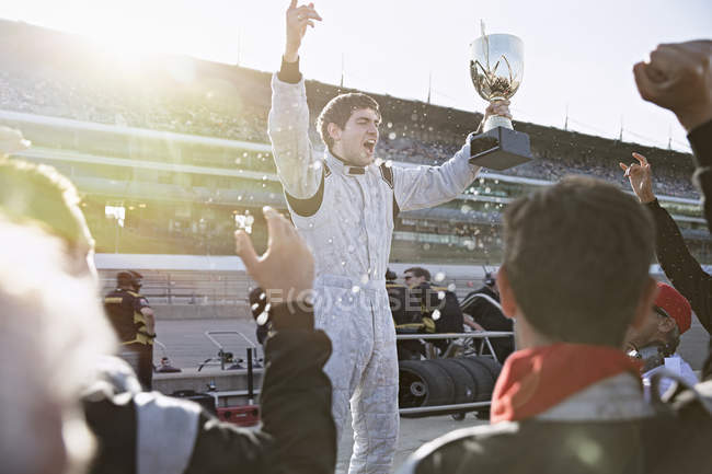 Formula one racing team cheering for driver with trophy, celebrating victory on sports track - foto de stock