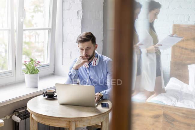 Чоловік працює на ноутбуці в квартирі — стокове фото