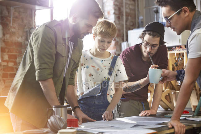 Designers meeting, reviewing plans in workshop — Stock Photo