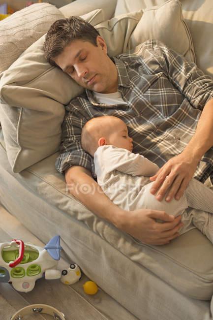 Père épuisé et bébé fils dormant sur le canapé — Photo de stock