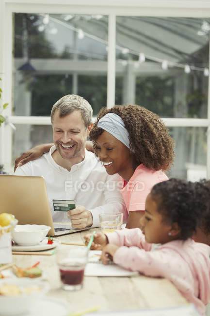Multi-ethnic young family online shopping with credit card at laptop — Foto stock