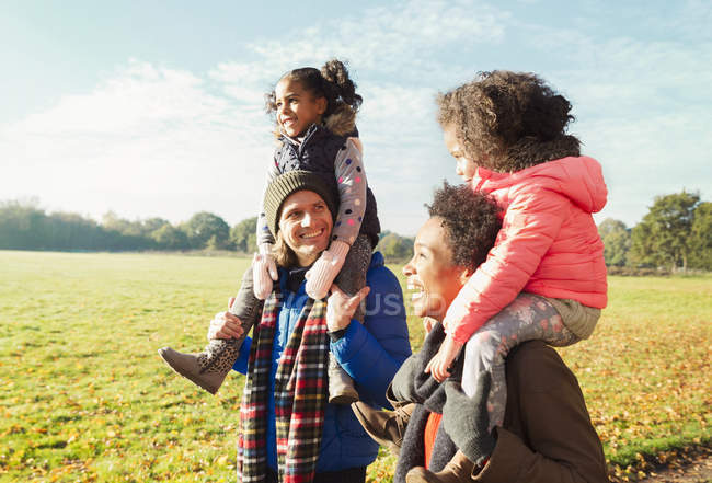 Батьки, які перевозять дочок на плечах у Сонячний Осінній Парк — стокове фото