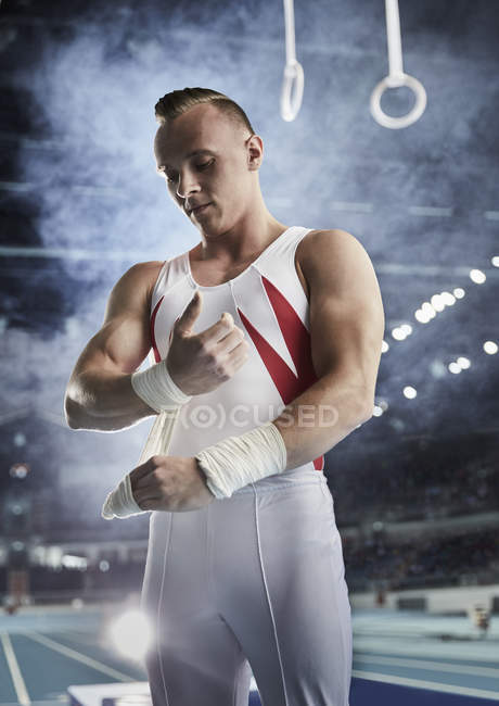 Male gymnast wrapping wrists below gymnastics rings in arena — Stock Photo