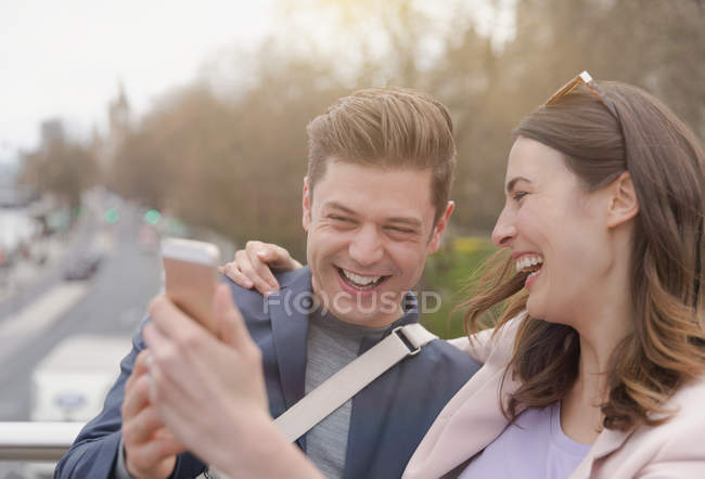 Laughing couple taking selfie with camera phone — Stock Photo