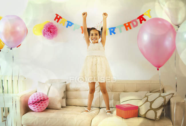 Portrait confident girl with arms raised on sofa at birthday party — Stock Photo