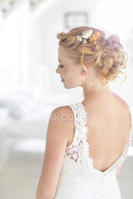 Young bride standing in sunny bedroom — Stock Photo