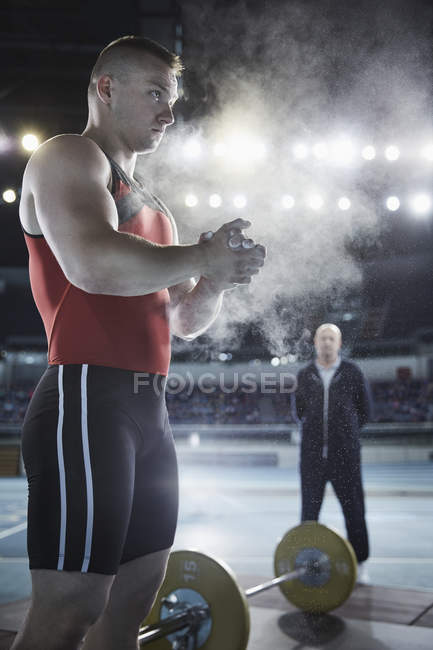 Coach watching male weightlifter applying chalk powder to hands at barbell — Stock Photo