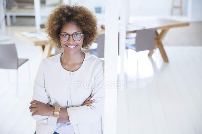 Porträt einer Frau, die sich an eine Säule im Büro lehnt und lächelt — Stockfoto
