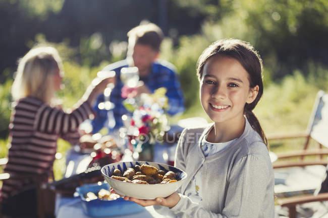 Портрет, улыбается девушка порции пищи в солнечном саду партии патио таблицы — стоковое фото