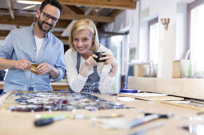 Smiling stained glass artists looking over project in studio — Stock Photo