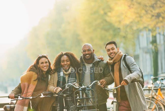 Porträt lächelnde Freunde Fahrrad fahren auf städtischen Herbststraße — Stockfoto