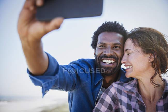 Affectueux, heureux couple multi-ethnique prenant selfie avec téléphone appareil photo — Photo de stock