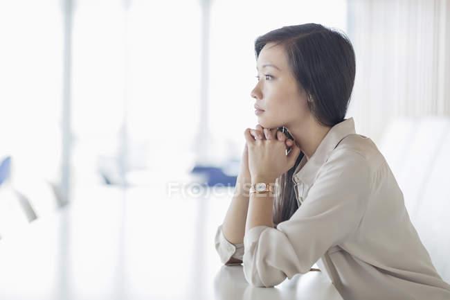 Donna d'affari pensierosa che distoglie lo sguardo nella sala conferenze — Foto stock