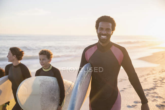 Portrait smiling, confident male surfer carrying surfboard with family on sunny summer sunset beach — Stock Photo