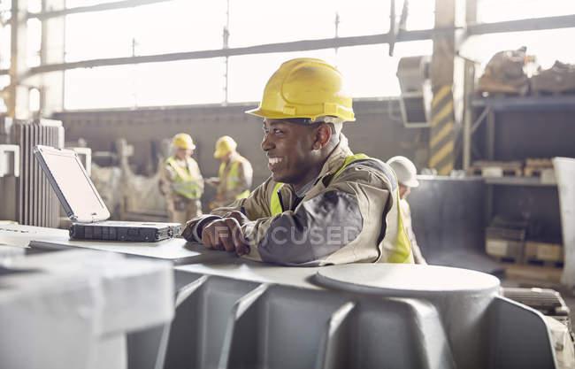 Lächelnder Stahlarbeiter schaut im Stahlwerk weg — Stockfoto