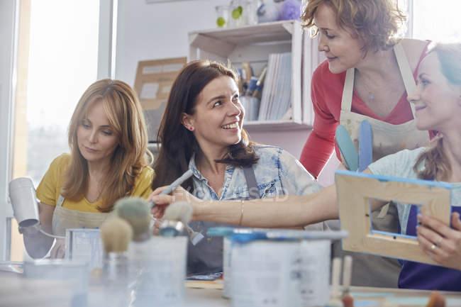 Instructrice aidant les élèves à peindre des cadres dans un atelier de classe d'art — Photo de stock