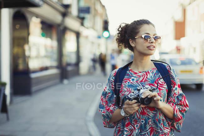 Jovem turista em óculos de sol com câmera na rua urbana — Fotografia de Stock